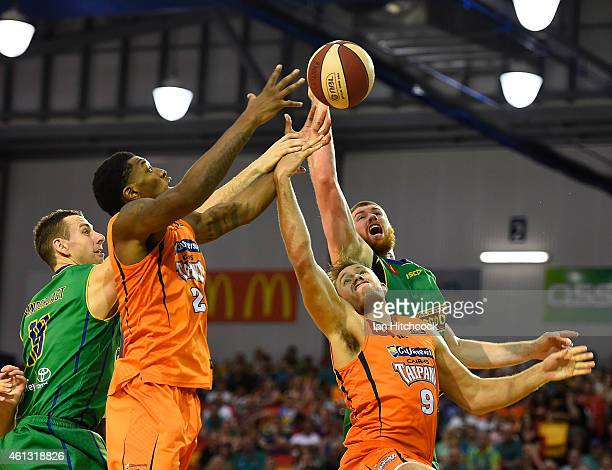 Torrey Craig and Mitch Young of the Taipans contest the ball with Greg Vanderjagt and Brian Conklin of the Crocodiles during the round 14 NBL match...