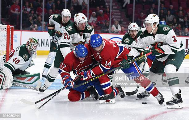 Torrey Mitchell and Tomas Plekanec of the Montreal Canadiens fight for the puck against Charlie Coyle and Ryan Suter of the Minnesota Wild in the NHL...