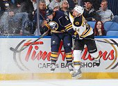 Torrey Mitchell of the Buffalo Sabres and Dennis Seidenberg of the Boston Bruins collide along the boards on October 30 2014 at the First Niagara...