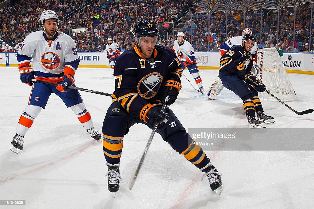 Torrey Mitchell #17 of the Buffalo Sabres skates to the corner between teammate Zemgus Girgensons #28 and Frans Nielsen #51 of the New York Islanders on April 13, 2014 at the First Niagara Center in Buffalo, New York.