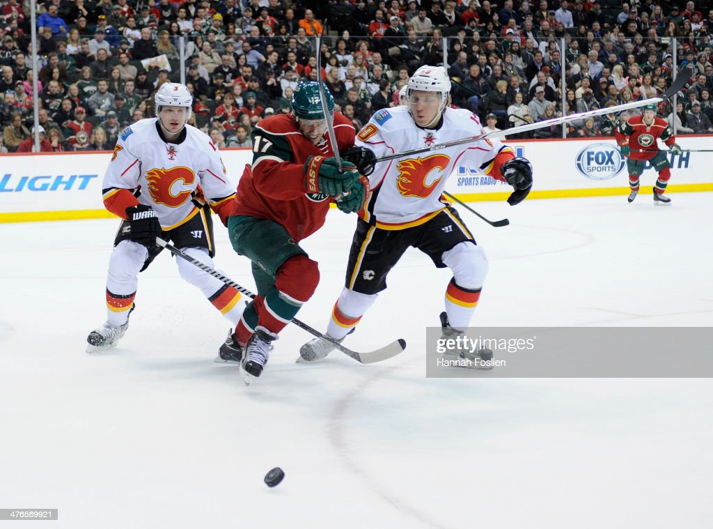 Torrey Mitchell of the Minnesota Wild along with Ladislav Smid and Markus Granlund of the Calgary Flames skate after the puck during the second...