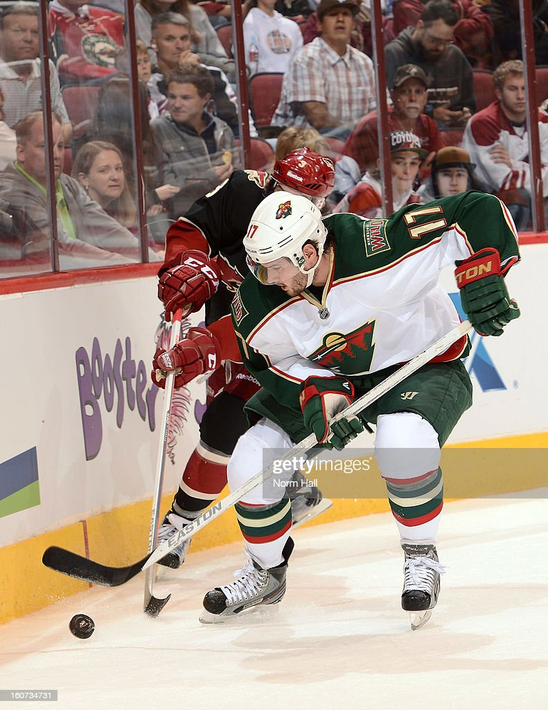 Torrey Mitchell #17 of the Minnesota Wild and Keith Yandle #3 of the Phoenix Coyotes battle for the puck along the boards during the first period at Jobing.com Arena on February 4, 2013 in Glendale, Arizona.