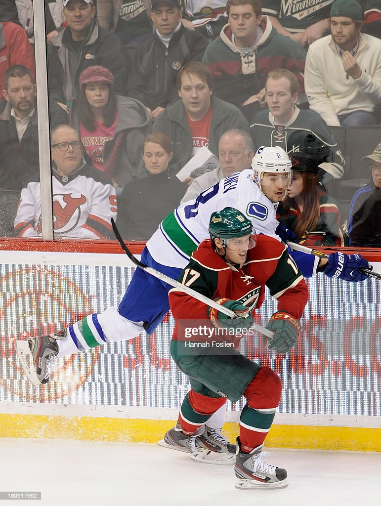 Torrey Mitchell #17 of the Minnesota Wild checks Chris Tanev #8 of the Vancouver Canucks into the boards during the third period of the game on February 7, 2013 at Xcel Energy Center in St Paul, Minnesota. The Canucks defeated the Wild 4-1.