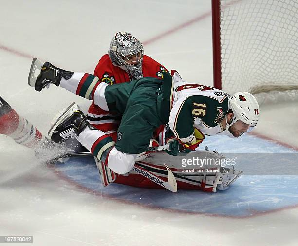 Torrey Mitchell of the Minnesota Wild collides with Corey Crawford of the Chicago Blackhawks after trying to shoot in Game One of the Western...