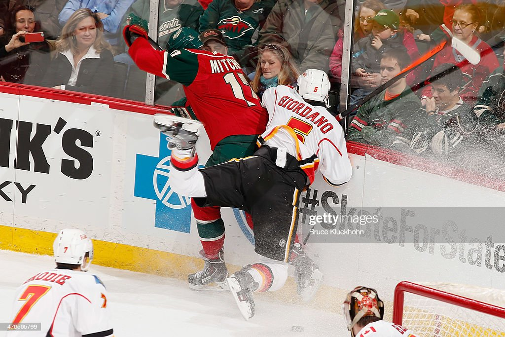 Torrey Mitchell #17 of the Minnesota Wild collides with Mark Giordano #5 of the Calgary Flames during the game on March 3, 2014 at the Xcel Energy Center in St. Paul, Minnesota.
