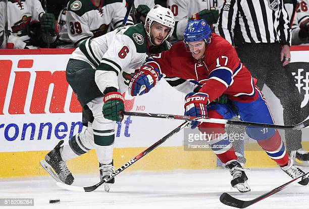Torrey Mitchell of the Montreal Canadiens and Marco Scandella of the Minnesota Wild fight for the puck in the NHL game at the Bell Centre on March 12...