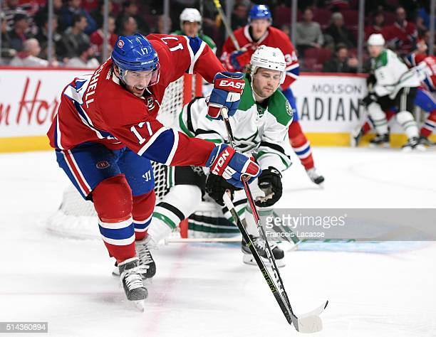 Torrey Mitchell of the Montreal Canadiens passes the puck against pressure from Kris Russell of the Dallas Stars in the NHL game at the Bell Centre...