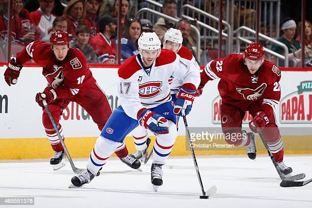 Torrey Mitchell of the Montreal Canadiens skates with the puck ahead of David Moss and Craig Cunningham of the Arizona Coyotes during the second...