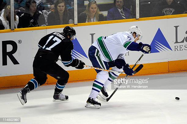 Torrey Mitchell of the San Jose Sharks hinders the progress of Daniel Sedin of the Vancouver Canucks in the second period in Game Four of the Western...