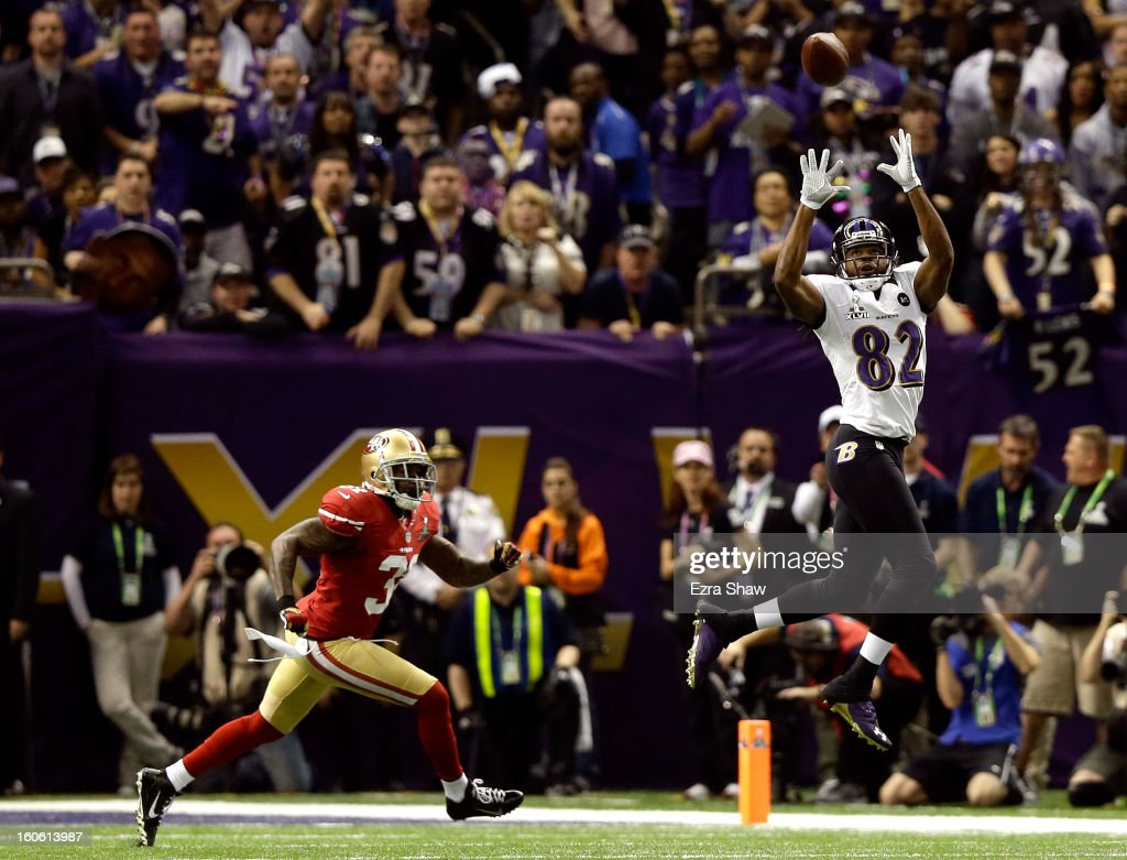 Torrey Smith of the Baltimore Ravens makes a catch in the first quarter against Donte Whitner of the San Francisco 49ers during Super Bowl XLVII at...