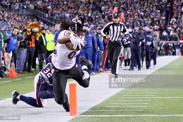 Torrey Smith of the Baltimore Ravens scores a touchdown in the third quarter against Devin McCourty of the New England Patriots during their AFC...