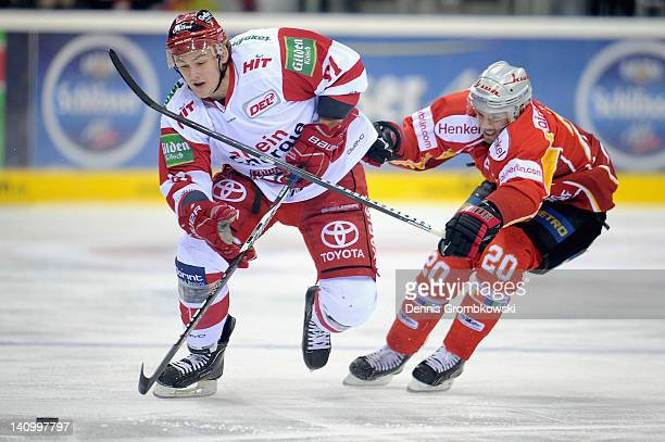 Torsten Ankert of Cologne is challenged by Connor James of Duesseldorf during the DEL match between DEG Metro Stars and Koelner Haie at ISS Dome on...