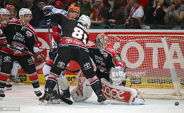 Torsten Ankert of Koeln and Brent Raedeke of Iserlohn Roosters battle for the puck during the DEL match between Koelner Haie and Iserlohn Rooster at...