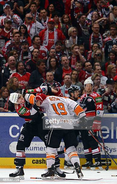 Torsten Ankert of Koeln fights with Marco Rosa of Wolfsburg during the DEL semi final playoff game between Koelner Haier and Grizzly Adams Wolfsburg...