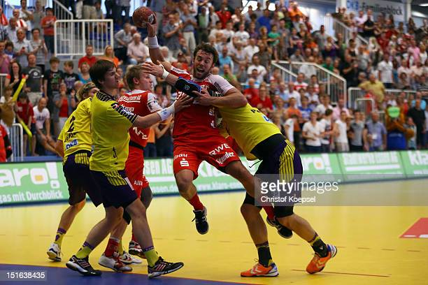 Torsten Laen of Berlin and Ivan Nincevic of Berlin challenge Philipp Poeter of Essen during the DKB Handball Bundesliga match between TUSEM Essen and...