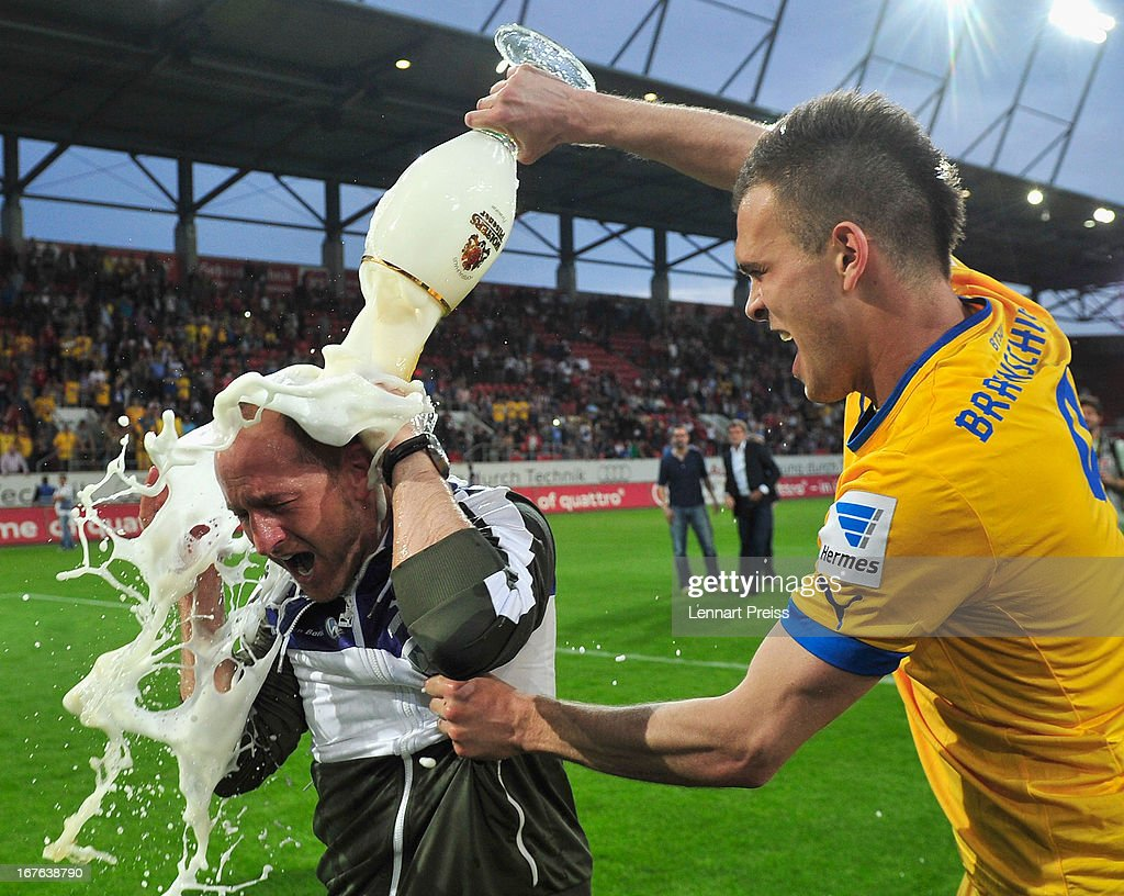 Torsten Lieberknecht (L), head coach of Braunschweig, has beer poured over him by Orhan Ademi as they celebrate promotion to the 1. Bundesliga, after the 2. Bundesliga match between FC Ingolstadt and Eintracht Braunschweig on April 26, 2013 in Ingolstadt, Germany.