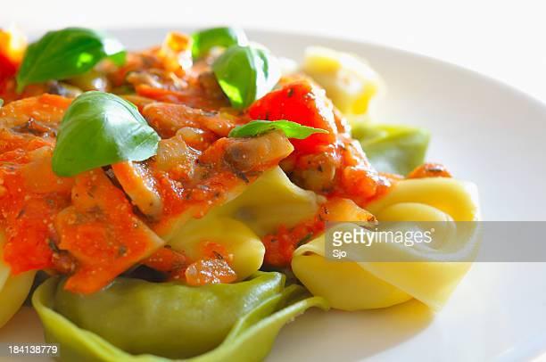 Eine Nahaufnahme von einem Tomaten sauce und Basilikum-tortellini auf Weiß