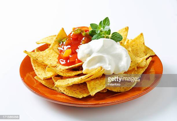 Tortilla chips with salsa dip and cream