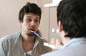 Tortured sleepy only waking man in front of the mirror with a toothbrush in his mouth