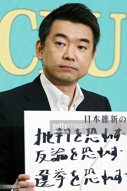Toru Hashimoto copresident of the Japan Restoration Party holds a sign featuring a slogan during a debate at the Japan National Press Club in Tokyo...