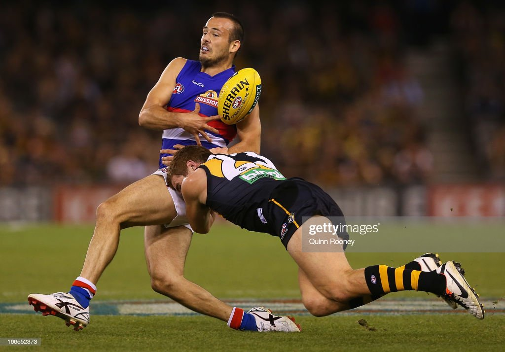 Tory Dickson of the Bulldogs is tackled by Daniel Jackson of the Tigers during the round three AFL match between the Richmond Tigers and the Western Bulldogs at Etihad Stadium on April 14, 2013 in Melbourne, Australia.