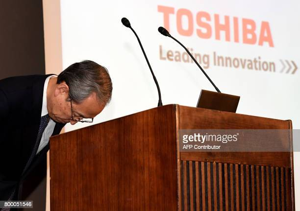 Toshiba corp president Satoshi Tsunakawa bows while delivering his speech during a press conference at the company's headquarters in Tokyo on June 23...