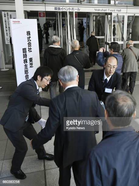 Toshiba Corp shareholders enter the venue of their meeting at Makuhari Messe in Chiba east of Tokyo on March 30 2017 The struggling electronics maker...