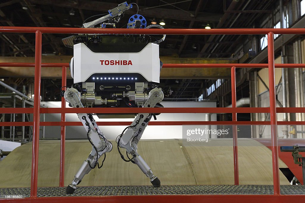 A Toshiba Corp. tetrapod robot walks along a catwalk at the company's Yokohama Complex in Yokohama City, Kanagawa Prefecture, Japan, on Wednesday, Nov. 21, 2012. Toshiba's new robot was developed to work in areas too dangerous for humans. Photographer: Akio Kon/Bloomberg via Getty Images