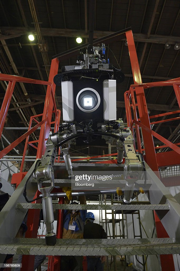 A Toshiba Corp. tetrapod robot walks up stairs at the company's Yokohama Complex in Yokohama City, Kanagawa Prefecture, Japan, on Wednesday, Nov. 21, 2012. Toshiba's new robot was developed to work in areas too dangerous for humans. Photographer: Akio Kon/Bloomberg via Getty Images