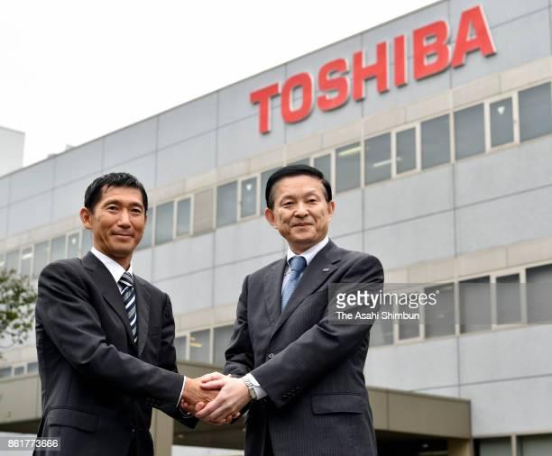 Toshiba Memory President Yasuo Naruke and Bain Captial Japan chief Yuji Sugimoto shake hands in front of the Yokkaichi Factory on October 13 2017 in...