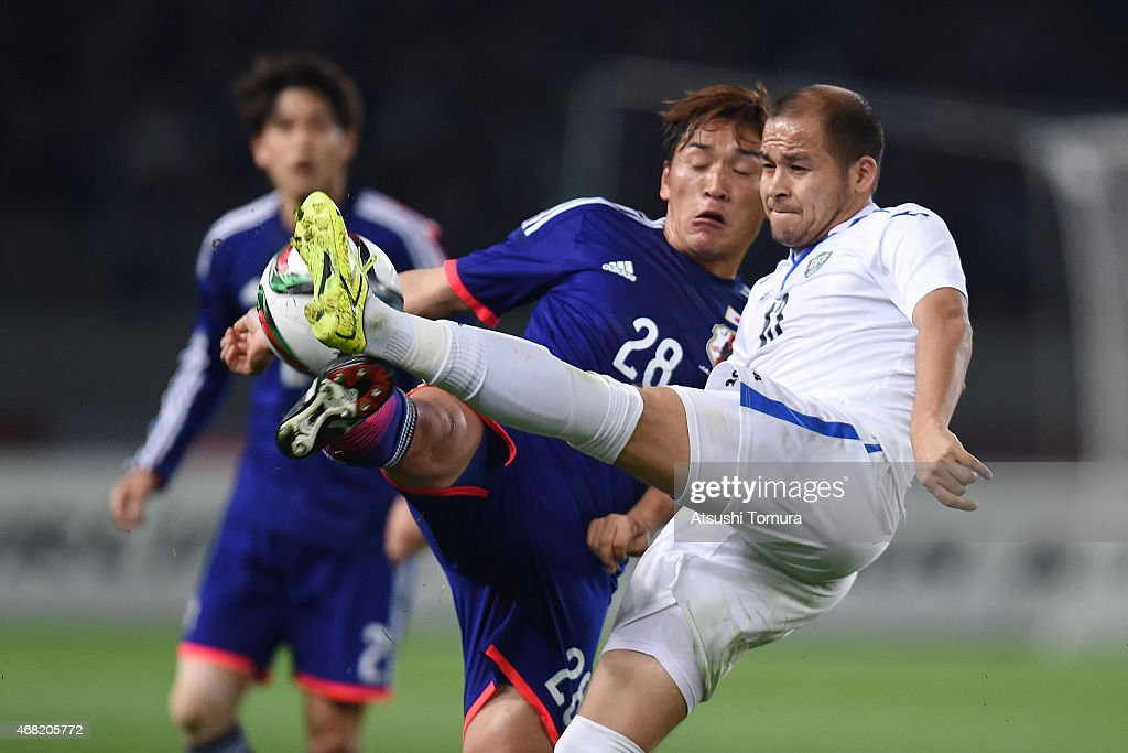 Toshihiro Aoyama (L) of Japan and Lutfulla Turaev (R) of Uzbekistan compete for the ball during the international friendly match between Japan and Uzbekistan at Ajinomoto Stadium on March 31, 2015 in Tokyo, Japan.