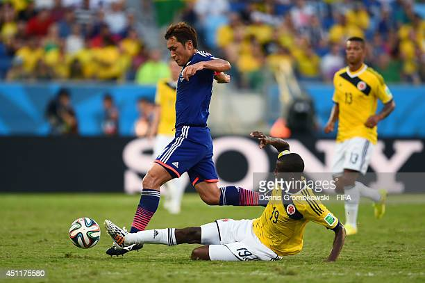 Toshihiro Aoyama of Japan is tackled by Adrian Ramos of Colombia during the 2014 FIFA World Cup Brazil Group C match between Japan and Colombia at...