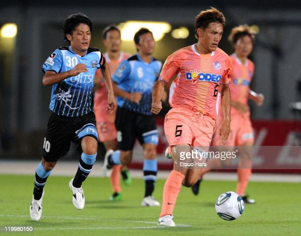 Toshihiro Aoyama of Sanfrecce Hiroshima and Ryota Oshima of Kawasaki Frontale compete for the ball during the Yamazaki Nabisco Cup 1st round second...