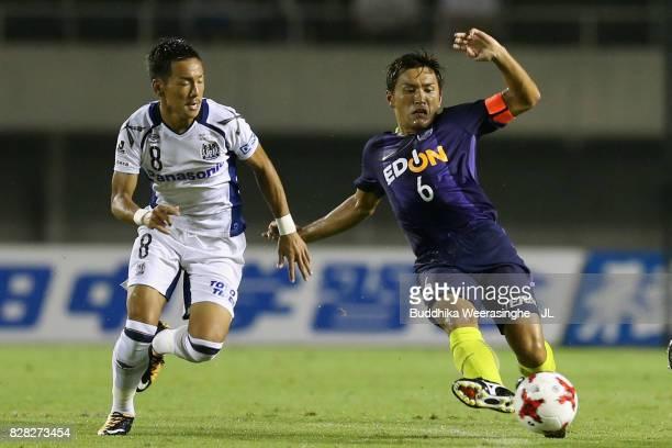Toshihiro Aoyama of Sanfrecce Hiroshima and Yosuke Ideguchi of Gamba Osaka compete for the ball during the JLeague J1 match between Sanfrecce...