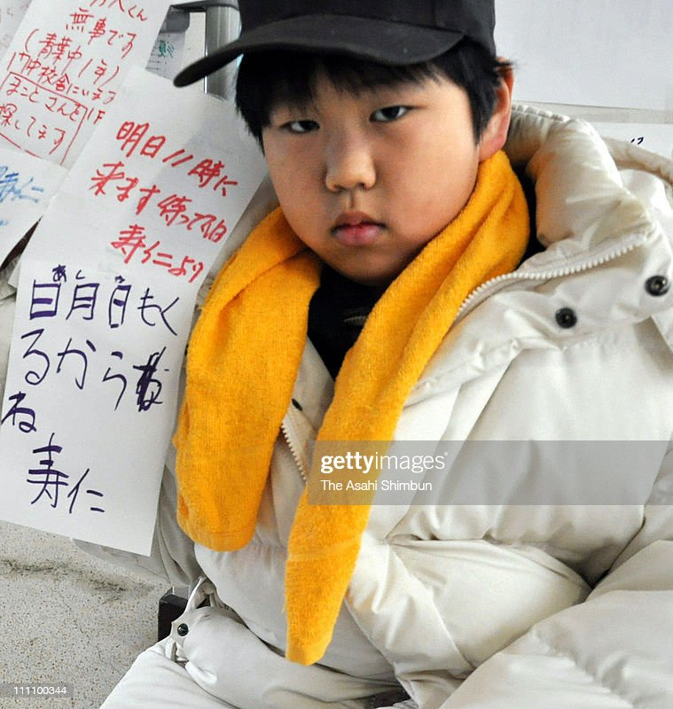 Toshihito Aisawa walks around the evacuation center holding banners writing his missing family members names at Kadonowaki Junior High School on March 15, 2011 in Ishinomaki, Miyagi, Japan. The 9-year-old boy, missing parents, grandmother and two cousins were caught by the huge tsunami on the way to an evacuation center. The quake struck offshore at 2:46pm local time, triggering a tsunami wave of up to 10 metres which engulfed large parts of north-eastern Japan. The death toll is currently unknown, with fears that the current hundreds dead may well run into thousands.
