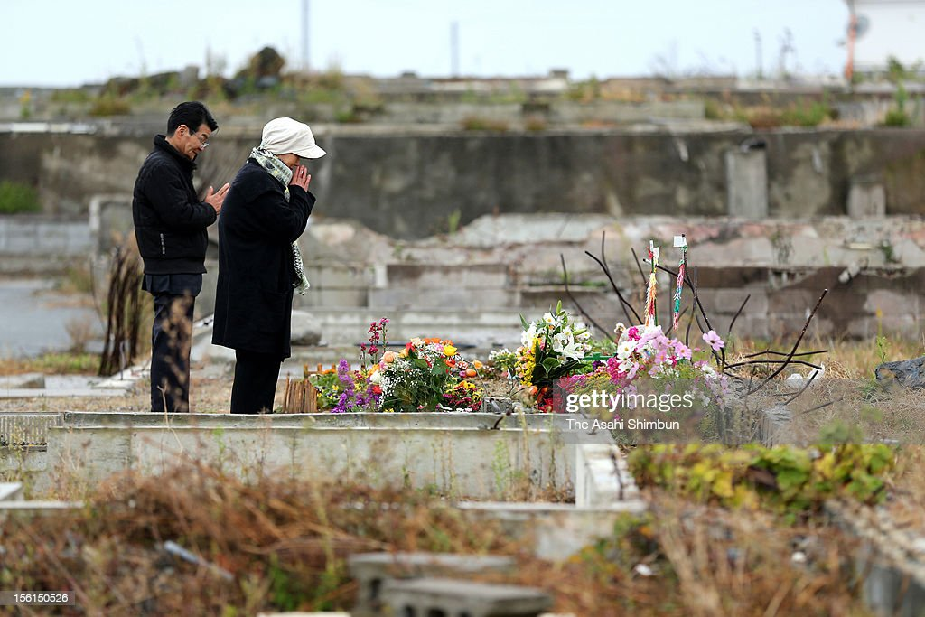 Toshimori Nobuhiro (71) and his wife Yoko (69) pray for the victims of tsuami at the destroyed Hisanohama area on November 11, 2012 in Iwaki, Fukushima, Japan. They have made flowerbed to commemorate the victims. Japan marks 20 months anniversary of the Great East Japan earthquake and following tsunami, occurred on March 11, 2011.