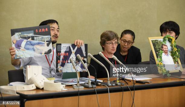 Toshio Hasegawa professor of health sciences at Kyorin University holds up photos as he speaks during a press coference at the Ministry of Health...