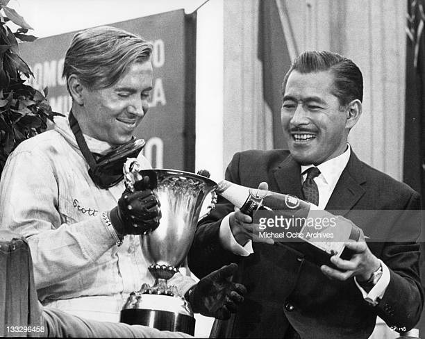 Toshiro Mifune fills Brian Bedford trophy cup with champagne in a scene from the film 'Grand Prix' 1966