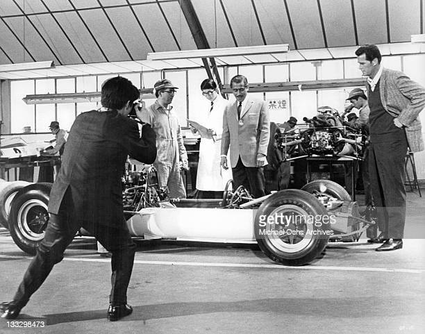 Toshiro Mifune has a showing of his new Yamura racing car at his English factory in a scene from the film 'Grand Prix' 1966