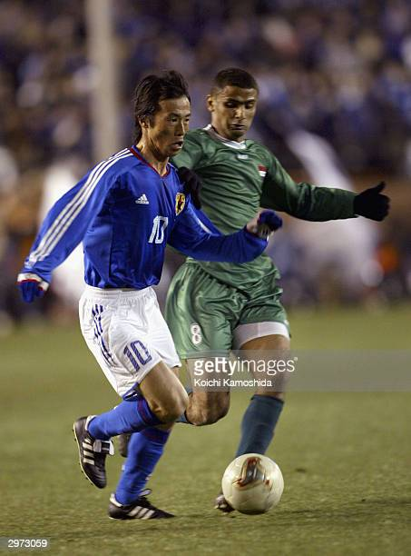 Toshiya Fujita of Japan is challenged by Ahmed S Alwan of Iraq during the friendly match between Japan and Iraq played at the Tokyo National Stadium...
