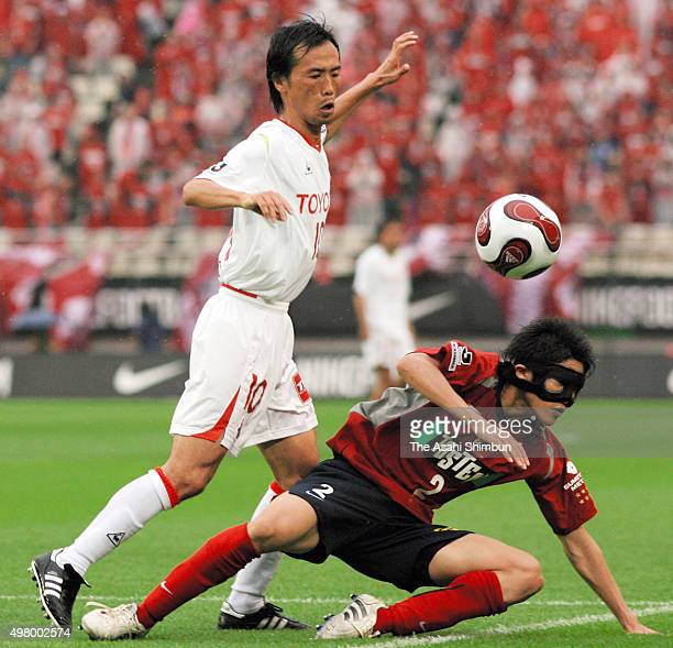 Toshiya Fujita of Nagoya Grampus Eight and Atsuto Uchida of Kashima Antlers compete for the ball during the JLeague match between Kashima Antlers and...