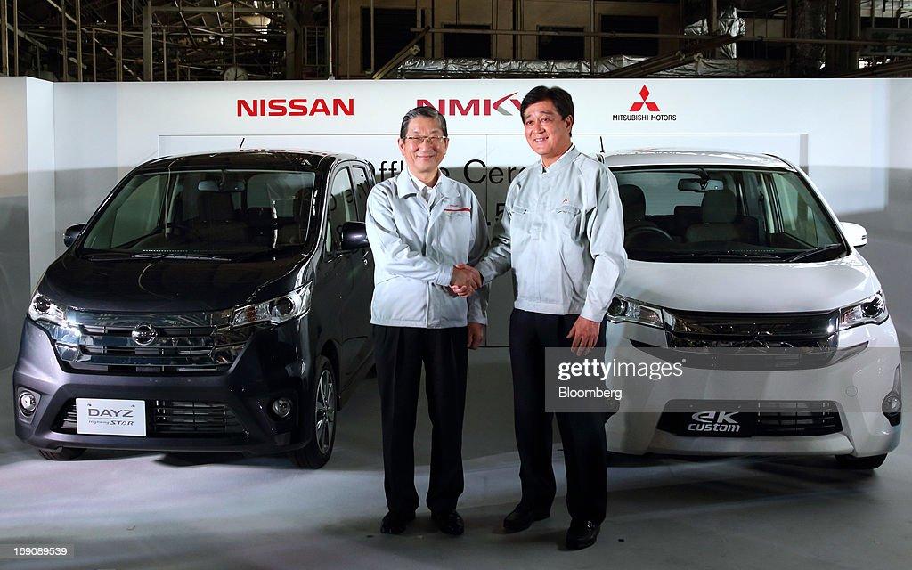 Toshiyuki Shiga chief operating officer of Nissan Motor Co left shakes hands with Osamu Masuko president of Mitsubishi Motors Corp during their...