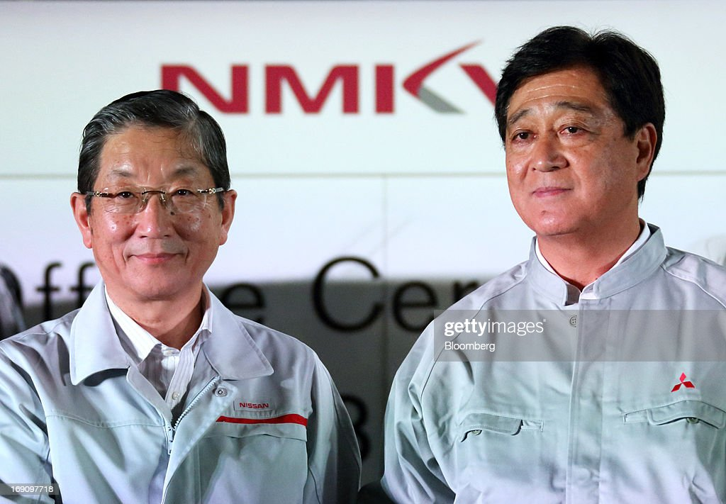 Toshiyuki Shiga chief operating officer of Nissan Motor Co left stands with Osamu Masuko president of Mitsubishi Motors Corp at their companies' line...