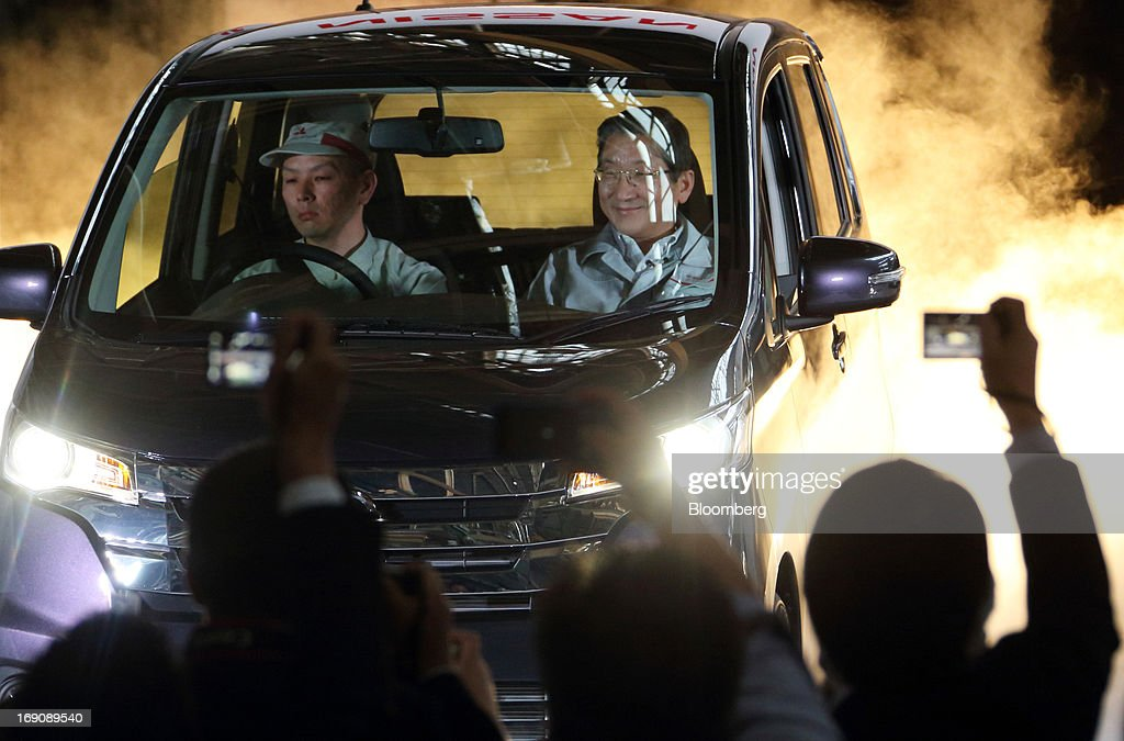 Toshiyuki Shiga chief operating officer of Nissan Motor Co right rides on the passenger seat of the Nissan DAYZ minicar during the line off of the...