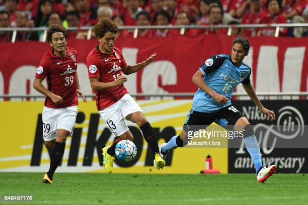 Toshiyuki Takagi of Urawa Red Diamonds and Elsinho of Kawasaki Frontale compete for the ball during the AFC Champions League quarter final second leg...