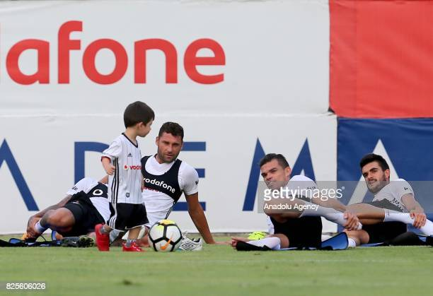 Tosic and Pepe of Besiktas play with Tolgay Arslan's son Kian during the training session ahead of the Turkcell Super Cup football match between...