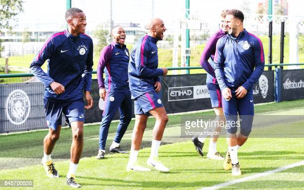 Tosin Adarabioyo jokes with Raheem Sterling Fabian Delph John Stones and Kyle Walker during training at Manchester City Football Academy on September...