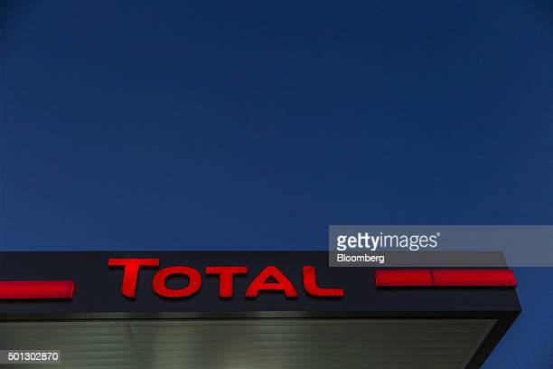 A Total logo sits illuminated above the forecourt of a gas station operated by Total SA in LucLaPrimaube near Rodez France on Friday Dec 11 2015 Oil...