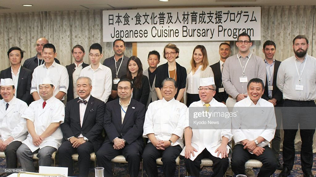 A total of 14 cooks from 11 countries and territories and other people pose for a photo during an opening ceremony at a hotel in Tokyo on June 30, 2016, to mark the launch of a training program aimed at promoting Japanese cuisine overseas. The cooks will be trained on the job at traditional Japanese restaurants in Kyoto and Tokyo for six months after learning basic Japanese language and culinary skills at cooking schools and elsewhere.