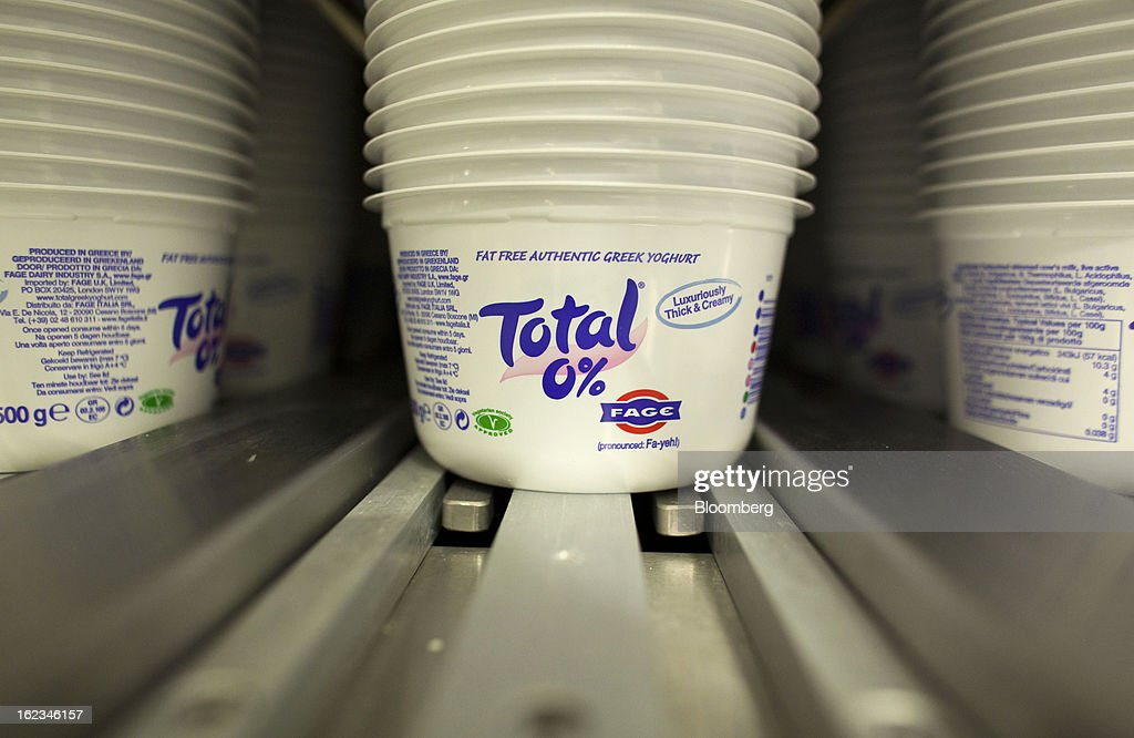 Total-branded yoghurt cartons stand in a machine before processing at the Fage Dairy Industry SA plant in Athens, Greece, on Thursday, Feb. 21, 2013. An October restructuring that placed Fage International SA's Greek units in a subsidiary called Fage Dairy Industry SA coincided with Coca-Cola Hellenic Bottling SA's plan to flee the epicenter of Europe's debt crisis by moving its main stock listing to London from Athens. Photographer: Kostas Tsironis/Bloomberg via Getty Images